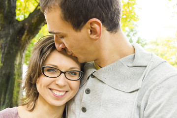 Portrait of love couple embracing outdoor looking happy