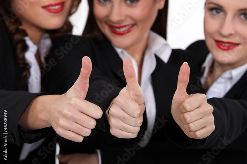 Three coworkers giving the thumb up.