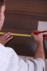 Man measuring slat of parquet