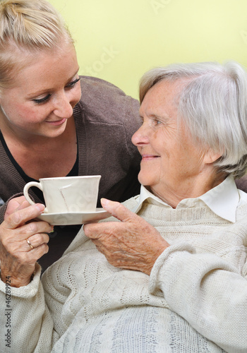 Senior woman with caregiver at home.