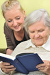 Senior woman with her caregiver in home reading book.