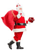 Santa Claus walking with bag and gift in his hands