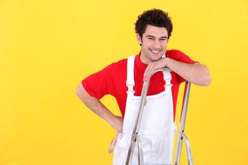 A painter standing on a ladder.