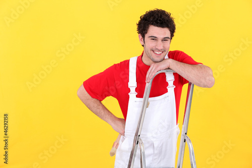 A painter standing on a ladder.