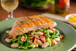 Grilled salmon with white beans, kale, and bacon.