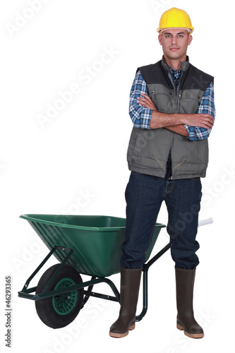 Man stood by empty wheelbarrow