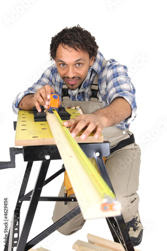 Carpenter carefully measuring plank of wood