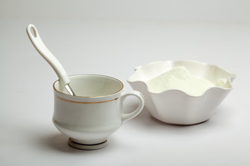 White cup, spoon and milk powder
