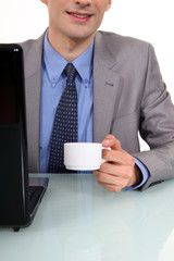 Businessman sat at laptop with morning coffee