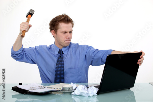 businessman ready to smash his laptop with a hammer