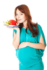 a pregnant woman with a plate of vegetables