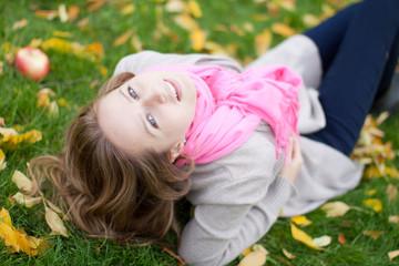 Молодая  женщина в осеннем парке с большим красным яблоком.