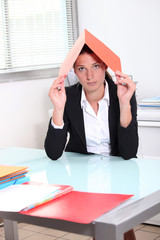 Young woman hiding under a file
