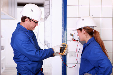 Electricians with voltmeter