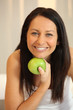 Portrait of a smiling woman with a Granny Smith apple