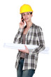 Woman in a hardhat with plans and a cellphone