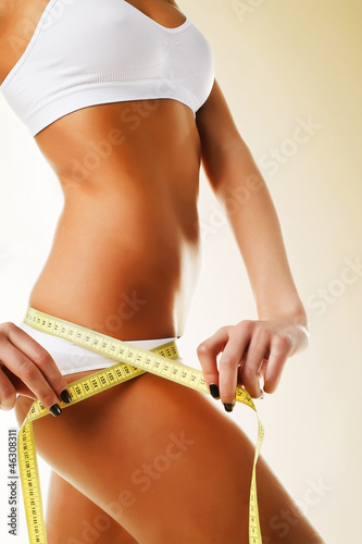 Beautiful sporty woman body in white with yellow measure