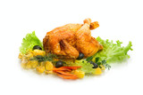Whole roasted chicken with vegetables on a white