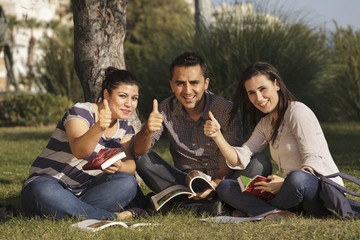Young students studying outdoors thumbsup