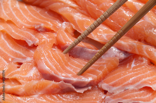 Close-up of salmon slices for sashimi with chopsticks