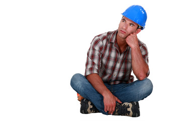 A pensive construction worker sitting on the floor.