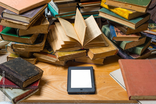 Ebook and old books on table