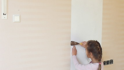 Girl removing a wallpaper in house.