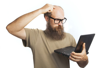 The bearded man with laptop is thinking
