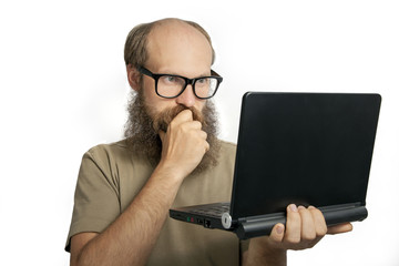 Bearded man looking and thinking at laptop