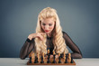 Beautiful blonde woman playing chess on dark background.