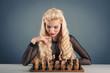 Beautiful blonde woman playing chess on dark background.