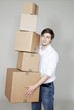 Handsome young man holding stack of cardboard boxes