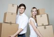 Happy young couple holding stack of cardboard boxes