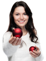 Young woman hands over a christmas bauble - isolated