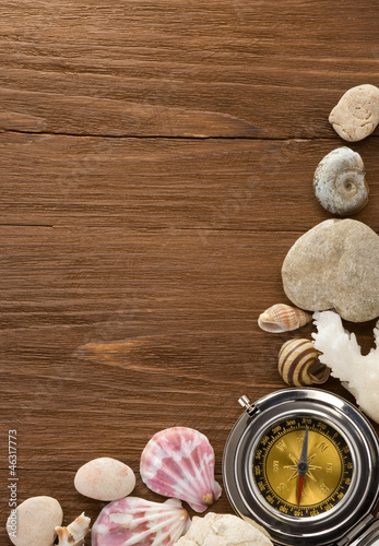 seashell and compass on wood