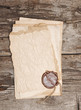 stack of old papers with a wax seal on wooden background