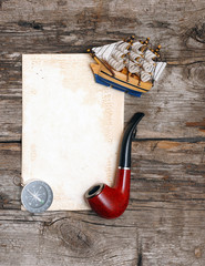 pipe, old paper, compass and model classic boat on wood backgrou
