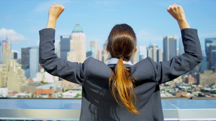Young Caucasian businesswoman celebrating success on rooftop