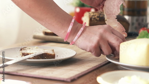 Woman hand putting ham on slice of bread, slow motion