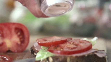 Hand sprinkle salt on sandwich, slow motion shot at 480fps