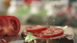 Hand sprinkle spices on tasty sandwich, slow motion shot at 240f