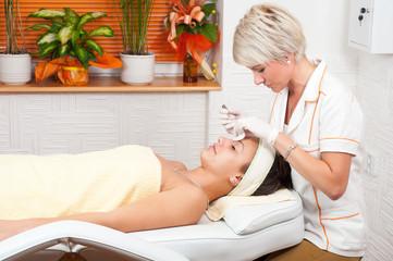 Beautiful young woman receiving a cosmetic treatment