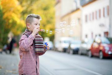 Junge spielt mit Seifenblasen