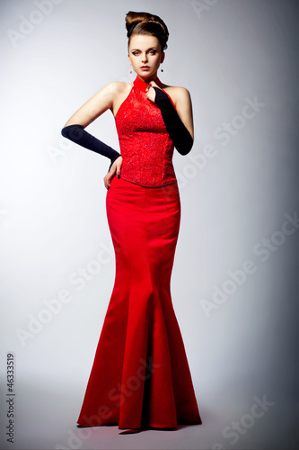 Graceful bride in black gloves and wedding red dress posing