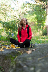 Young woman backpacker enjoying relaxation in the autumn forest
