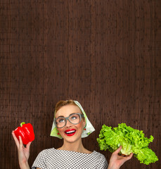 Funny woman cook holding salad and sweet pepper