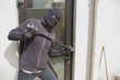 Robber breaking into house using crow bar