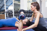 Female trainer helping client lifting weights