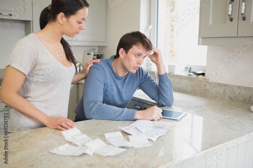 Two people using tablet pc to work out finances