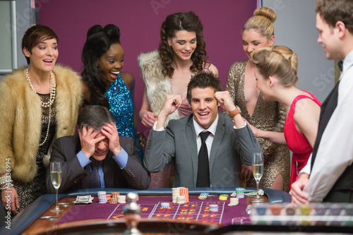 Man winning as another is losing at roulette table